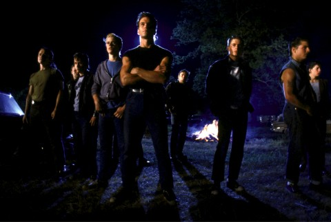 Full shot of (from left) Glenn Withrow as Tim Shepard, Emilio Estevez as Two-Bit Matthews, C. Thomas Howell as Ponyboy Curtis, Patrick Swayze as Darrel Curtis, Rob Lowe as Sodapop Curtis, Tom Cruise as Steve Randle.